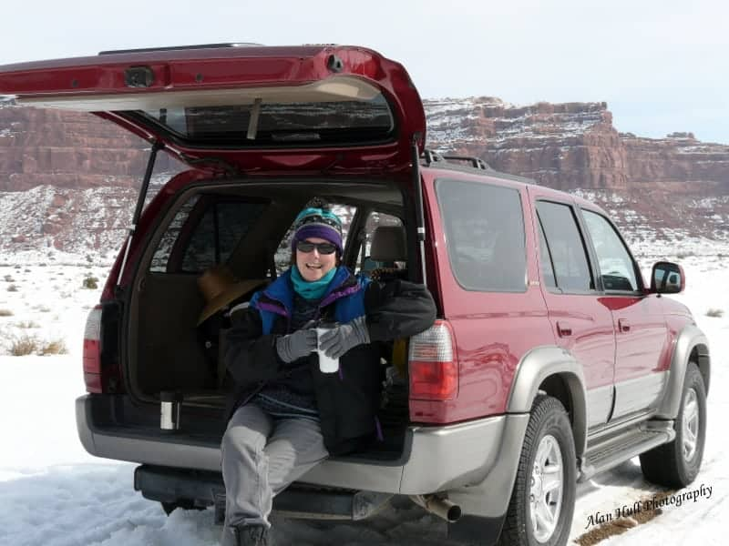 woman drinking coffee sitting on the tailgate of an suv in a snowy valley