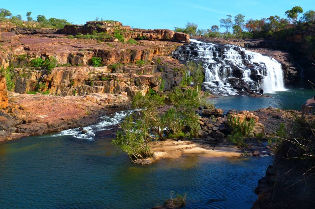 waterfalls flowing down a red stone cliff in Australia's Kimberley Region.