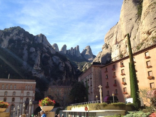 Pink buildings of the monastery surrounded by rock-topped mountains at Montserrat, Spain.