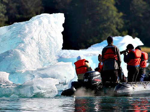 People in a zodiac photographing an iceberg on an active boomer travel adventure in Alaska.