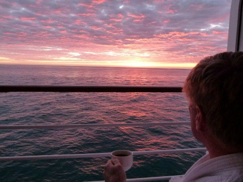 man sipping coffee looking at sunrise in South Pacific