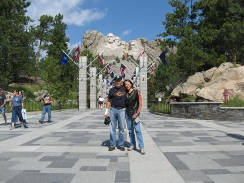 Boomer couple standing in front of Mt Rushmore.