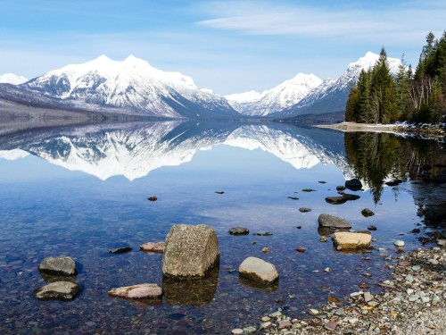 Snow-capped mountains overlook the clear waters of Lake McDonald in Glacier National Park.