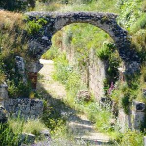 stone arch surrounded by grass and trees in Syracuse, Sicily