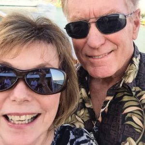 Boomer woman and man smile as their luxury cruise ship leaves port