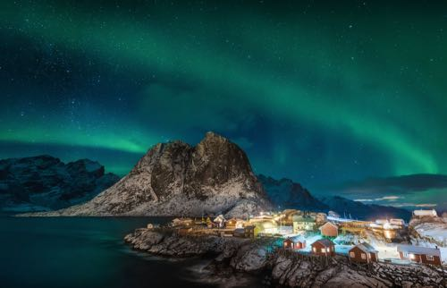 Northern lights over a village as seen on a northern lights cruise.