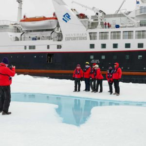 man taking photo of group standing on ice with cruise ship in background