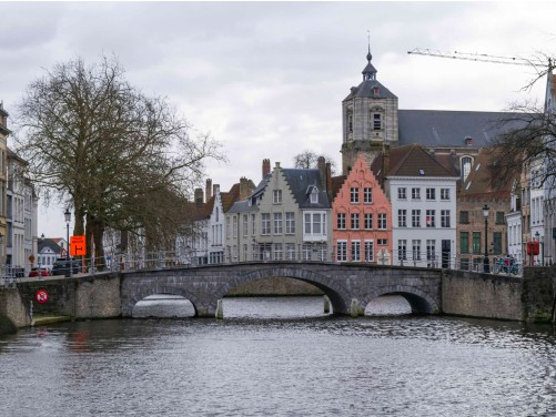 a bridge over a canal with buildings in the background