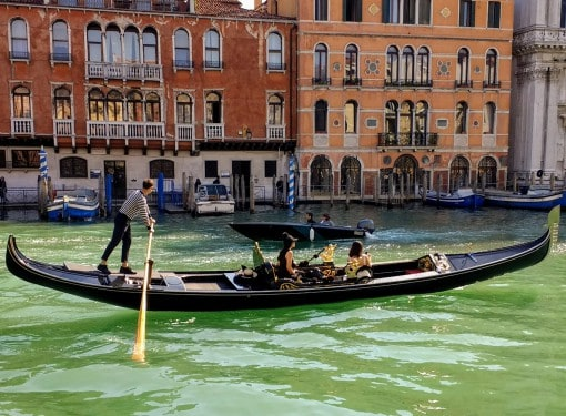 man steering a gondola with passengers inside