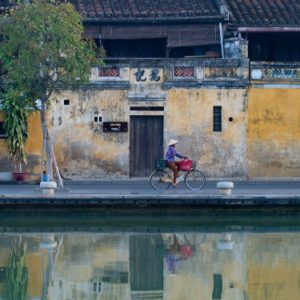 Woman wearing a non la, or conical hat, riding a bicycle in Hoi An Old Town in Vietnam. Her reflection in shown in the Thu Bon River.