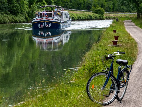 canal with cruise with bicycle in foreground