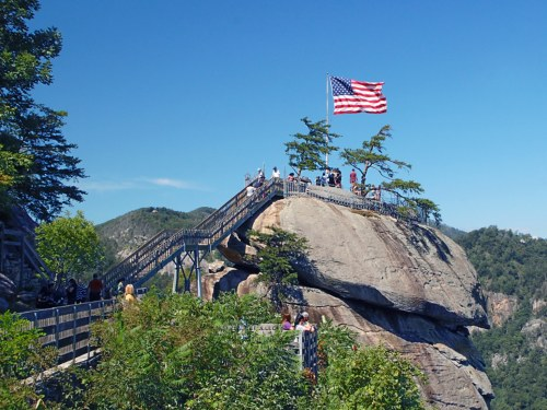 stairs leading up to large rock with american flag