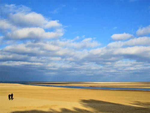 wide golden-sand beach with blue sky and clouds