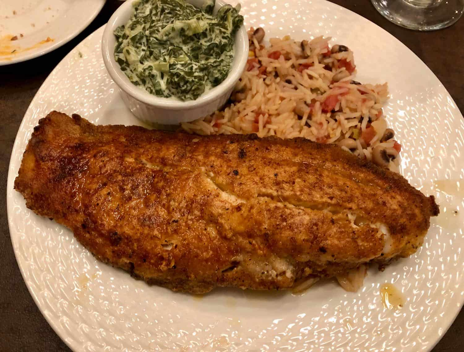 catfish, rice and creamed spinach on a white plate at Cafe Anchuca