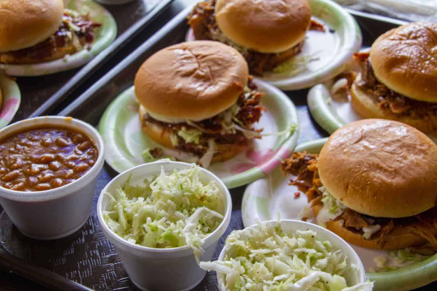 Barbecue sandwiches with cups of coleslaw and baked beans