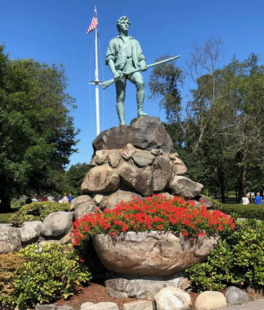 statue of an early American revolutionary surrounded by a rock base and red flowers