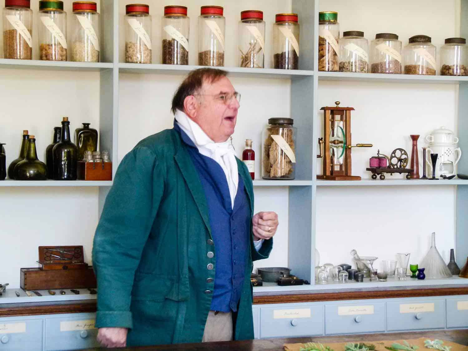 Man dressed in early American stands in front of jars of herbs in the Old Salem Apothecary