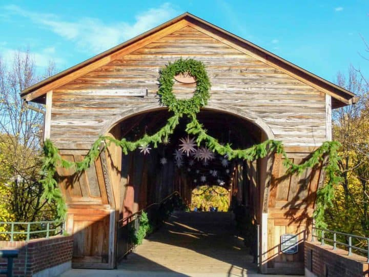 A brown covered bridge decorated with Christmas greenery