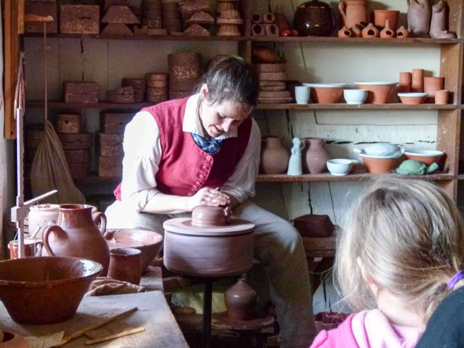 A woman dressed in early American clothes, sits behind a potters wheel making a pot while visitors watch.