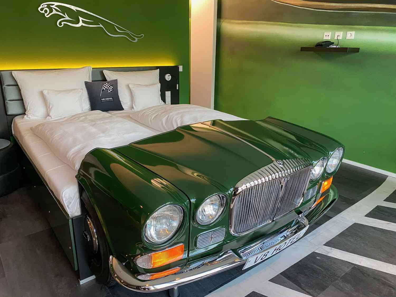 A bed made out of a green Jaguar car