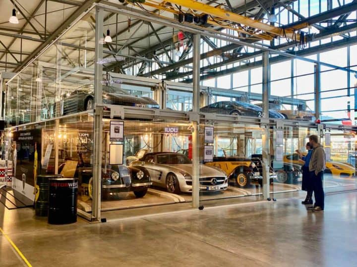 A car museum with cars housed in open bays protected by glass