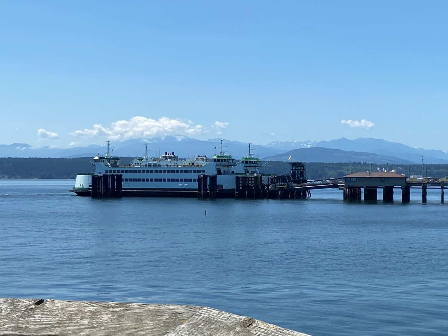 Blue water looks out onto a ferry at the dock with mountains in the distance