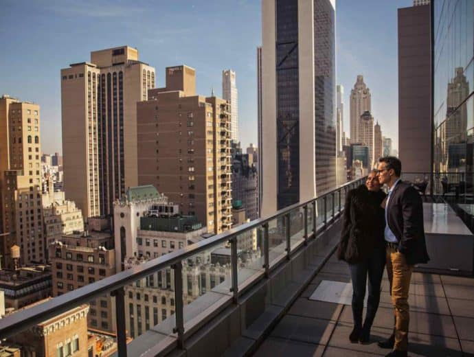 A couple standing on a balcony overlooking a city