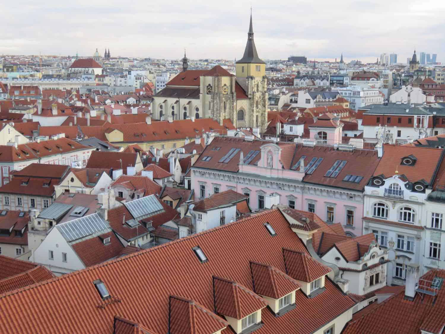 A Prague view that overlooks red tile roofs and church towers