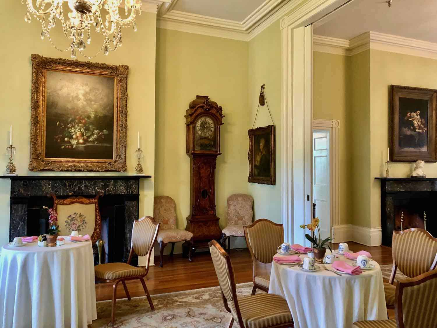 Tables in a colonial era room covered with linen tablecloths, set for tea