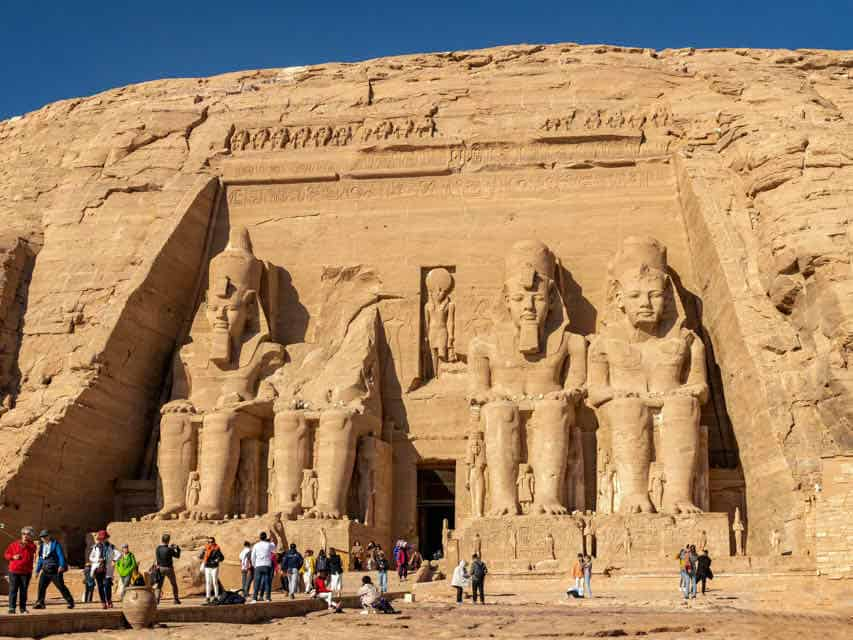 Beige colored sandstone temple with seated statutes in front