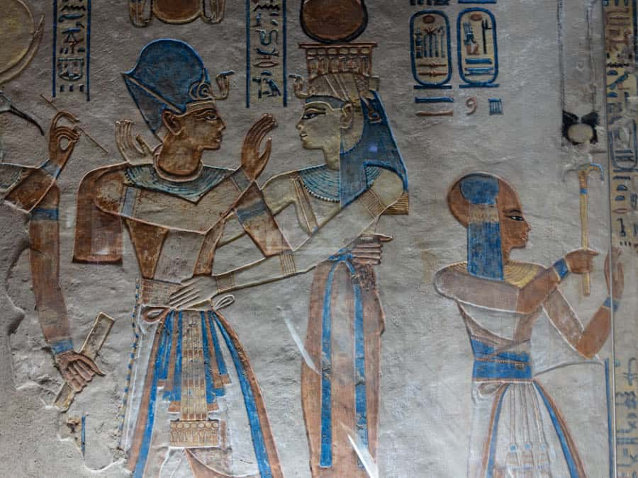 Blue and peach-colored figures on an Egyptian tomb
