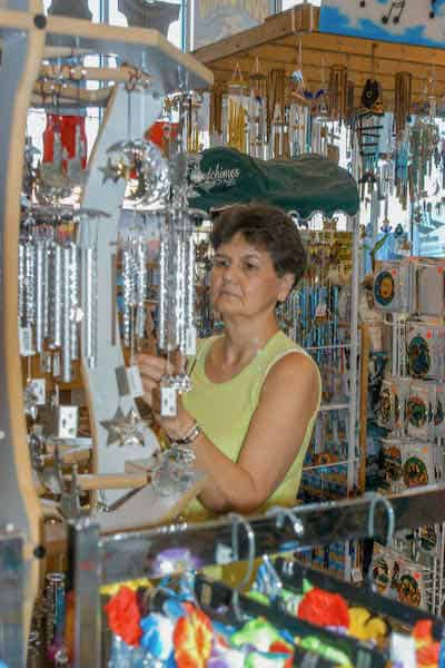 woman in a store looking at wind chimes