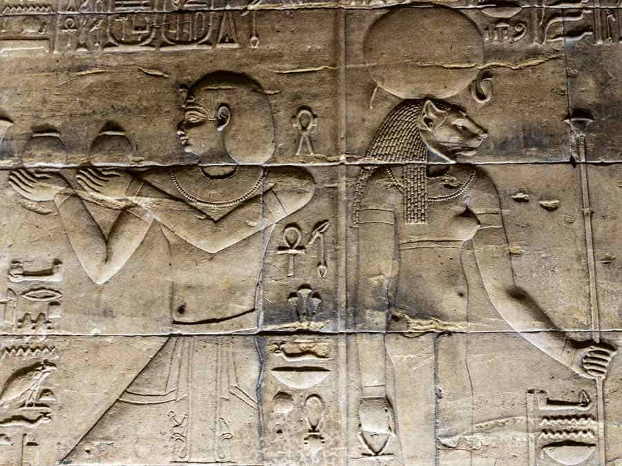 Carved relief panels of an Egyptian and a woman wearing a cat head
