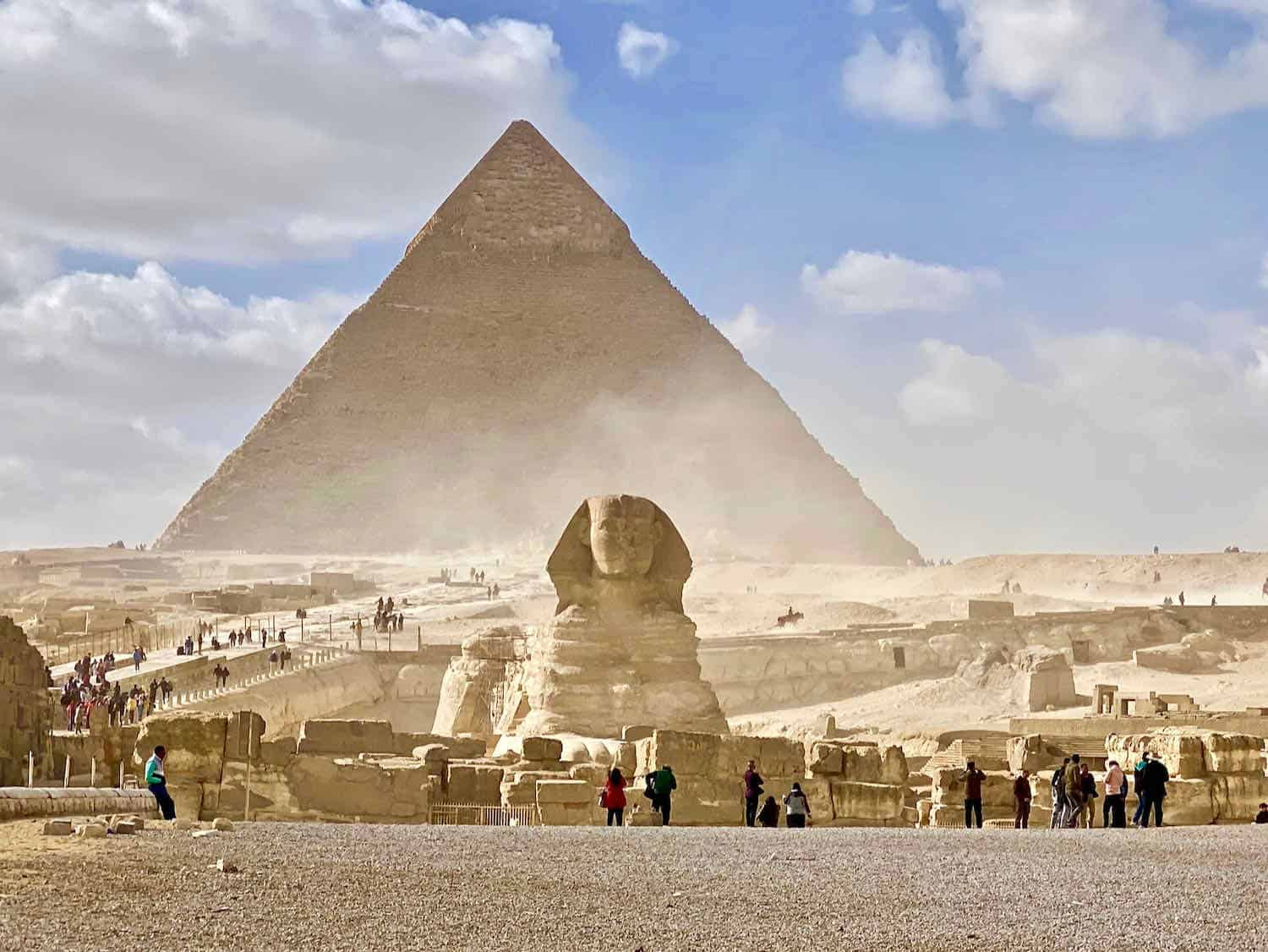 sphinx in front of a pyramid with dust blowing around
