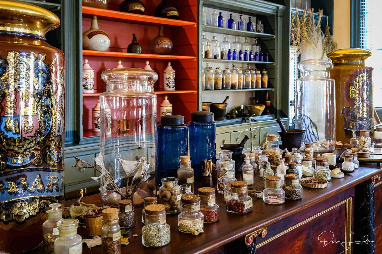 Colorful bottles on shelves behind a counter holding jars of treatments at a colonial American apothecary shop.