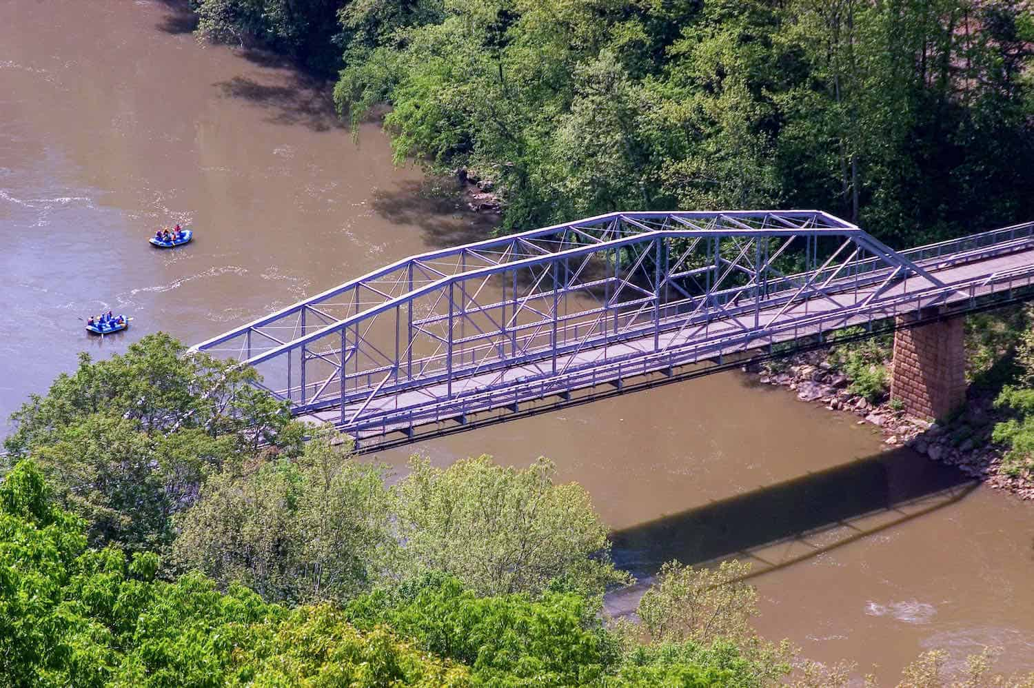 Iron bridge over a muddy river with rafters on the river.