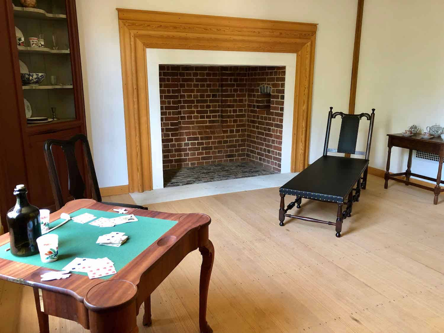 Colonial room with a large fireplace, wood chase and card table.