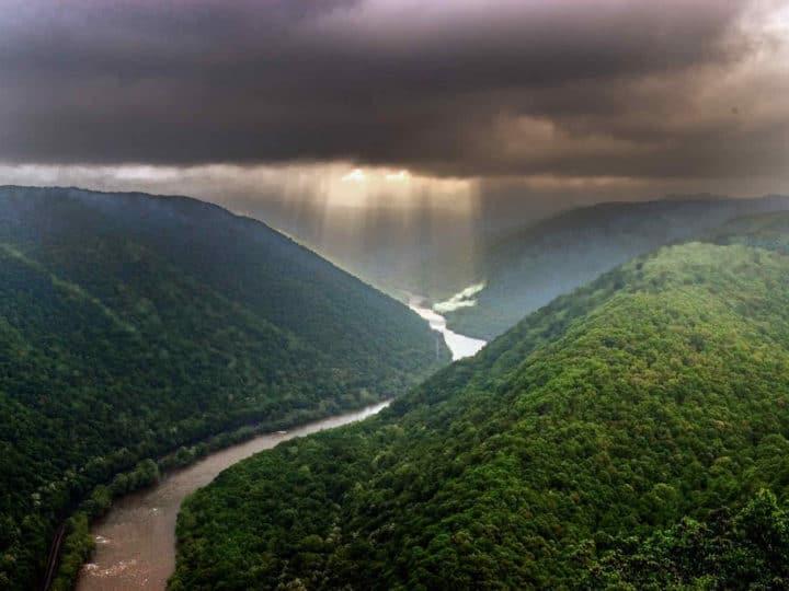 Light shafts stream through a storm cloud illuminating a river that flows between green mountains