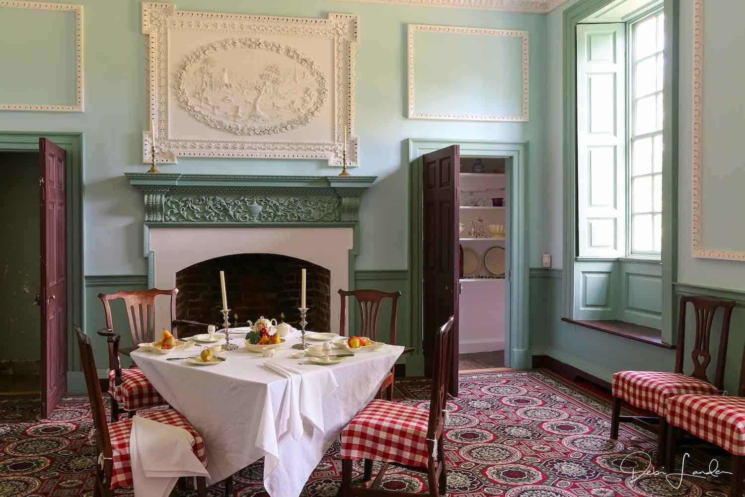 Colonial dining room with green walls and a red print carpet.