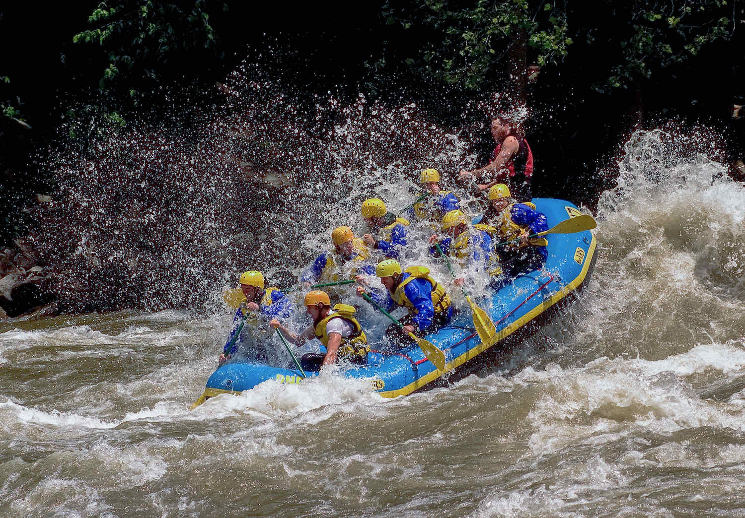 A blue river raft filled with people splashes through rapids on the New River.