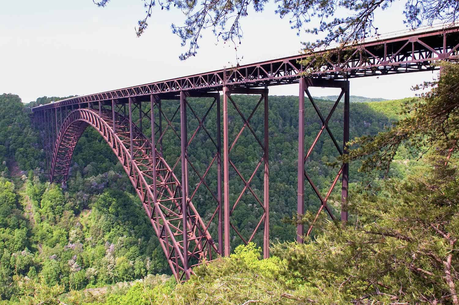 Rust-colored iron bridge stretching across the New River