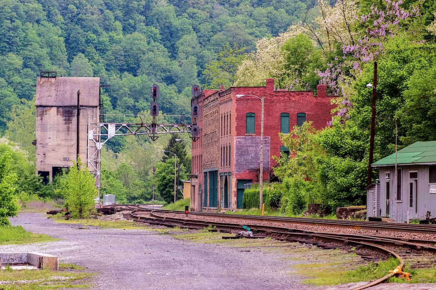 Railroad tracks curving between two abandoned buildings