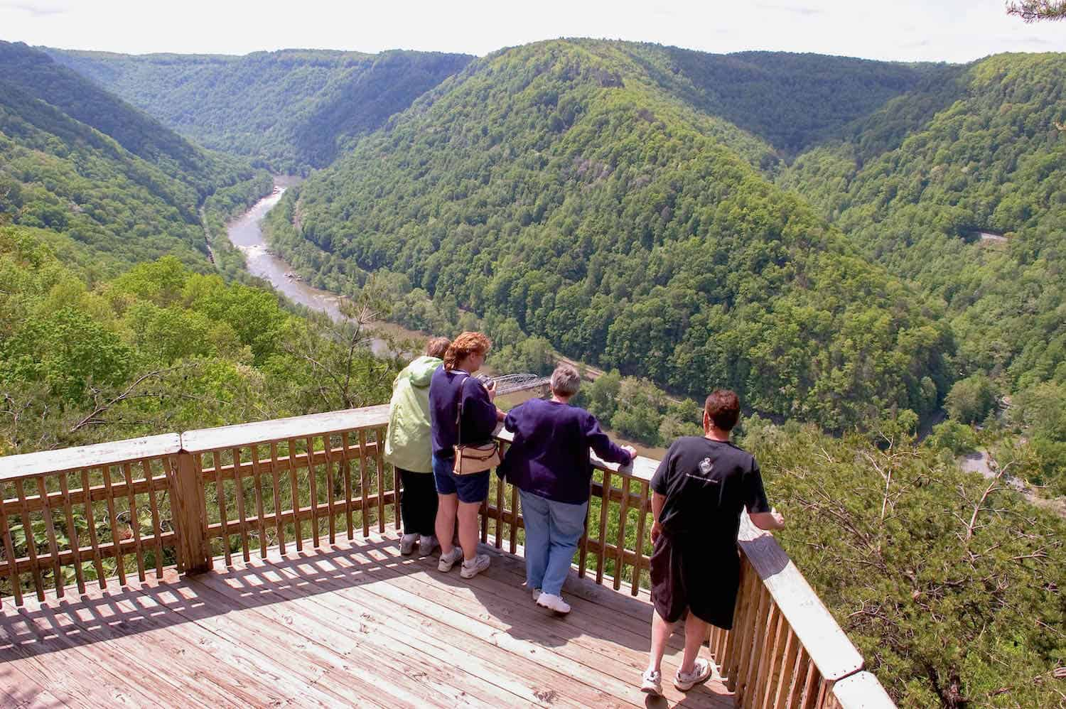 4 people standing at a wooden overlook viewing the river and mountain landscape at New River Gorge National Park.