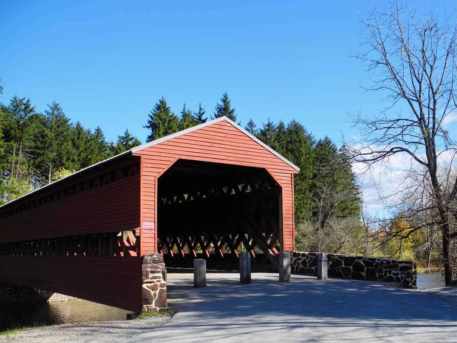 red covered bridge surrounded by trees with a blue sky overhead