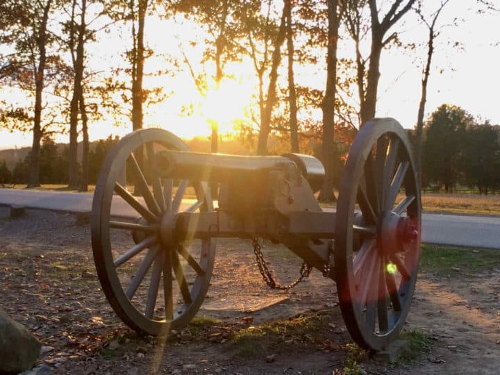 cannon with the sun setting behind it
