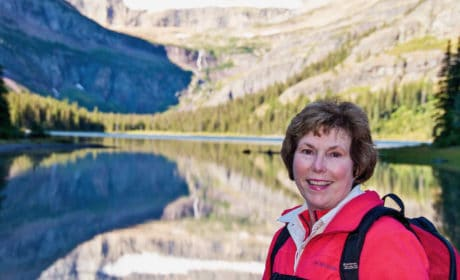 woman wearing a backpack in front of a lake with mountains behind