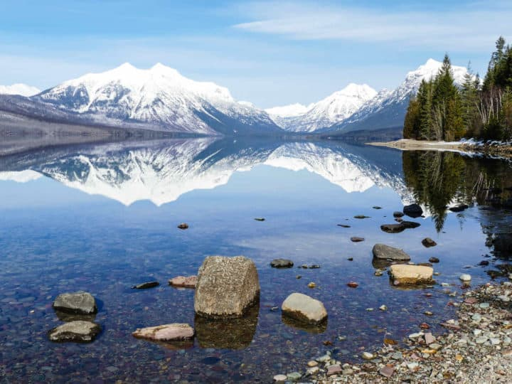 Snowcapped mountains reflected in a lake with rocks at the edge of the lake and trees to the right