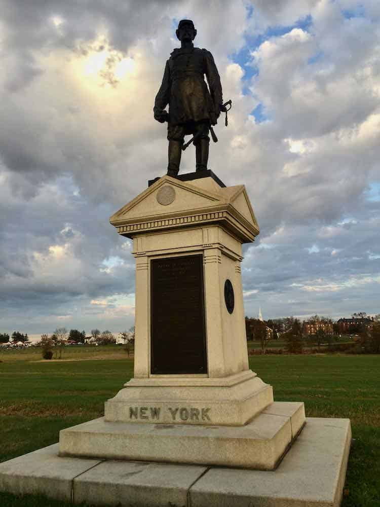 """statue of a soldier standing on a monument that says """"New York"""""""
