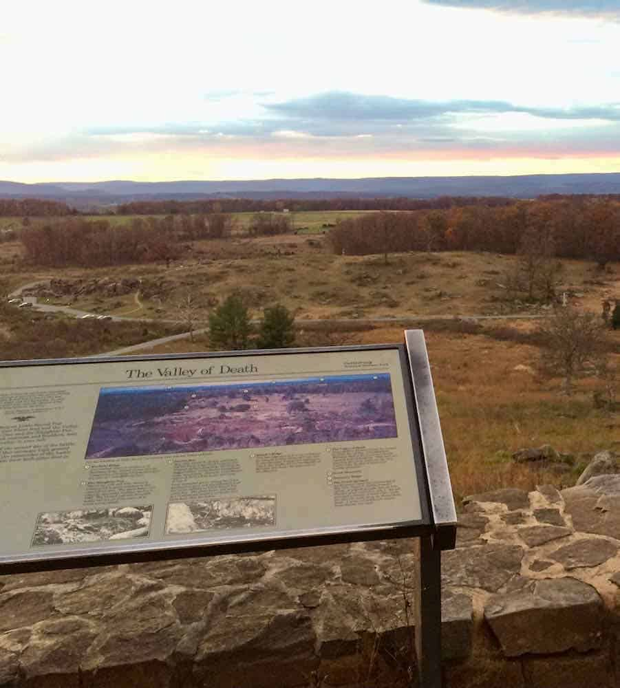 """Historical sign that says """"Valley of Death"""" looking over empty land where the battle of Gettysburg took place"""