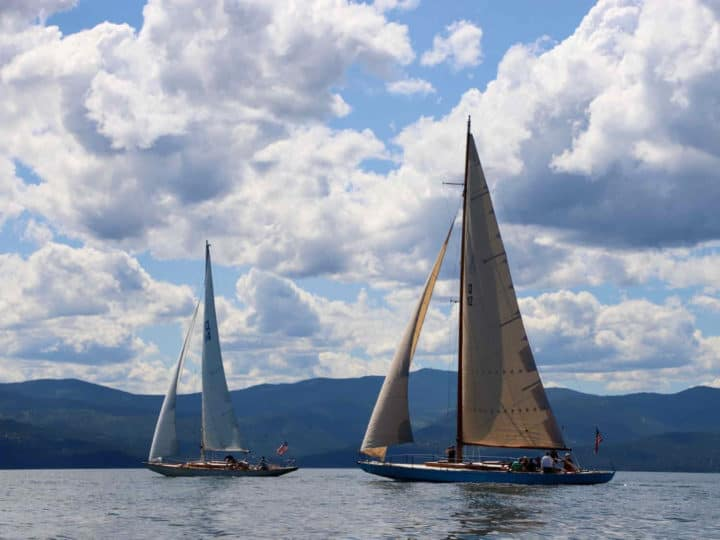 Two sailboats on Flathead Lake with lots of clouds in the sky.